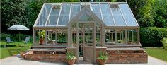 This Glass to Ground Greenhouse by Hartley Botanic features a vault barrel and central portico entrance for growing and preserving plants.