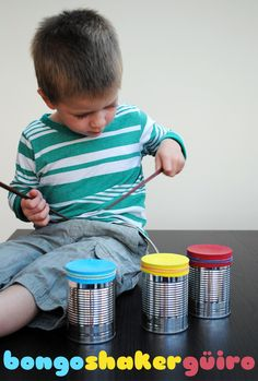 Tin can bongos, take empty tin cans, fill with rice, pasta, or beans, stretch a balloon over it, and wrap a rubber band around the top.