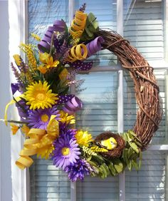 "Gold and Purple daisy's welcome the new season with fresh foliage on a 14"" rapevine wreath.  Add soem color and style to your front door and order this soon :)"