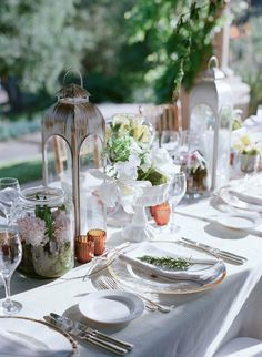 The long rehearsal dinner table was decorated down the center with rustic-style lanterns, glass jars filled with moss and pink florals, and white ceramic stands topped with moss and white flowers. #Centerpieces Photography: Elizabeth Messina. Read More: http://www.insideweddings.com/weddings/an-intimate-garden-themed-rehearsal-dinner-in-ojai-california/553/