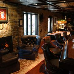 """brick wall, comfy bar chairs, comfy fireplace chairs with rug, nice bar counter edge detail, """"coffered"""" tin ceiling"""