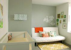 ellow gray green nursery design with soft gray green walls white modern futon, Anthropologie Coqo yellow floral rug, eclectic art gallery, Dwell Studio crib bedding, white Oeuf Sparrow crib, white modern futon and Ikea pillows.