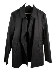 Abrigo azul marino tres cuartos, tiene solapas, con corchete en el cuello, botones marrones (unos ocultos y otros visibles). Tiene bolsillos.
