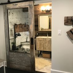 I want this gorgeous distressed barn door with vintage mirror inset in MY Rustic Glam bedroom!Modern Makeover of a 1937 Beach Bungalow by Kelly Canada owner of Abode Interiors