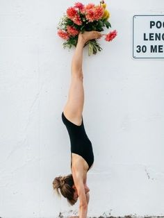 Bouquet of flowers held in the feet of a handstand. Yoga blooms.