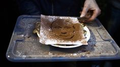 A Russian youth opposition activist makes a portrait of Vladimir Putin in cocoa powder on a pancake as they gather at the Chistiye Prudy, or Clean Ponds, where they vowed to continue the roving protest in Moscow, Saturday, May 12, 2012. (AP / Sergey Ponomarev)