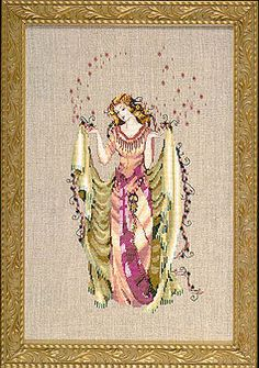 Forest Goddess - Mirabilia Cross Stitch Pattern. The Forest Goddess wears a berry colored satin gown with a moss green cloak. The model was stitched on 32 Ct. R