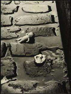 * Poupon sur les pavés (1938/1939) - Alfred Otto Wolfgang SCHULZE (dit WOLS) (1913-1951)très tôt passionné par les idées d'inventaire et de collection, se forme à Dresde dans un studio de portraits, puis entre en contact à Berlin en 1932 avec Laszlo Moholy-Nagy. Se rend peu après à Paris où il finira par s'installer, ayant décidé, après la guerre, de ne pas retourner en Allemagne. Il abandonne peu à peu la photographie et se consacre essentiellement au dessin et à la peinture.