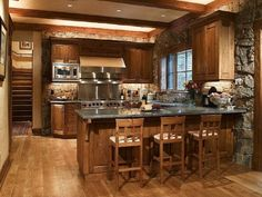Rustic Kitchen Featured Exposed Wooden Beam Also Stone Accent Wall And Cozy  Barstools Plus Steel Backsplash Behind Stove Idea