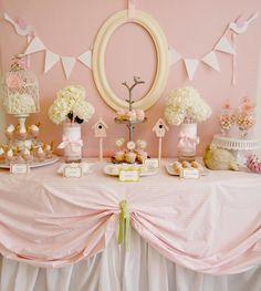 Chá de bebê para meninas, apenas uma simples moldura na parede rosa, com dois fios de Bunting combinando ao lado, toalhas lisas sobrepostas, formam a base pra mesa principal desta festa.