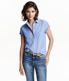 Blusa en tejido vaporoso de cambray de algodón con tapeta oculta, mangas cortas con dobladillo vuelto cosido, un bolsillo superior y bajo redondeado. Espalda ligeramente más larga.