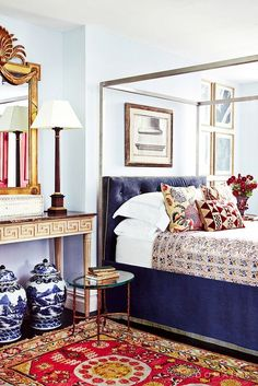 A tufted velvet headboard in a bold, solid color anchors a layered bedroom. Click for more ways to incorporate velvet into your home.