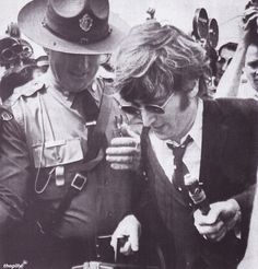 A Massachusetts State Trooper helps John through crowds of reporters as the Beatles change planes in Boston on their way to Chicago to kick ...