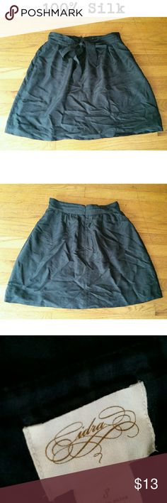 100% Silk Skirt Black silk skirt. 100% Silk shell. 100% Polyester lined. Ties in the front. Zipper in the back. Cidra Skirts Circle & Skater