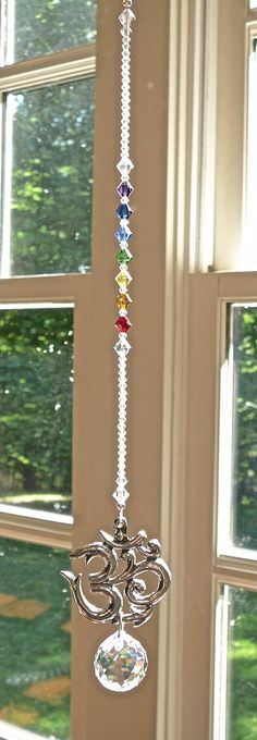"""Swarovski crystal and pewter om suncatcher, window decor, rainbow maker. This was created using: - 40x42mm (1.5"""") single-sided pewter om pendant - Chakra colored and clear Swarovski crystal beads - 20mm Swarovski clear (shown) or clear AB, logo etched crystal ball This is"""