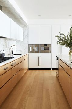 For those who still like to keep things light and airy, the light wood cabinets and floors—paired with white cabinets and white marble countertops and backsplash—make for a perfect compromise.