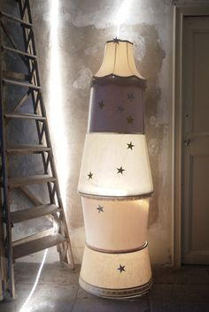 Could your consignment or thrift shop display window use a column of light to attract attraction after hours? How about this, asks Too Good to be Threw. Assorted orphan lampshades stacked & lit from within (don't you love the stars?)