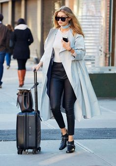 Gigi Hadid wears a neutral top, long gray coat, choker, leather pants, and ankle boot