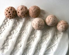This sculpture ball is very fun to use. You simply roll it firmly along clay to produce a pattern or texture that is a little different every time. You can also hold one side of the ball and press the other side into the clay for a concave stamped impression. This listing is for one (1) random pattern sculpture ball in bisque, approximately 3/4 in diameter. PLEASE NOTE: The pattern you will get is completely at random. I make these freely and rarely make the same design twice so they are…