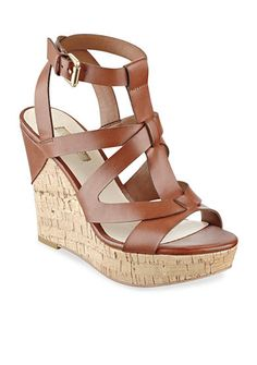 Heighten your wardrobe with these classic cork wedge sandals! Intricate brown strap detailing and gold-tone accents elevate this essential pair.