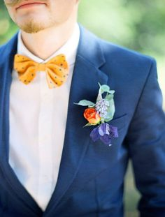 Groom in a navy suit with a yellow bowtie and bright boutonniere