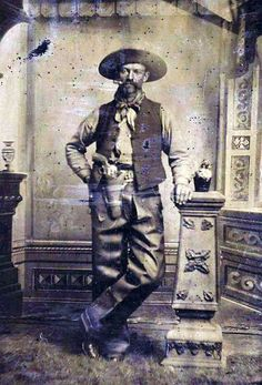 """COWBOY WITH COLT SINGLE ACTION ARMY - ca.1875-1890.  A wonderfully expressive tintype portrait of a rough Cowboy chomping on his cigar, featuring a nickel-plated Colt Single Action Army and holster rig. The cowboy has pulled the Colt """"Peacemaker"""" out of the holster and turned it around so that it faces outward. He is wearing leather chaps, a bandana, a hat, vest and boots. There is a whiskey bottle next to him on the pedestal. A great original tintype image of an iconic Western cowboy."""