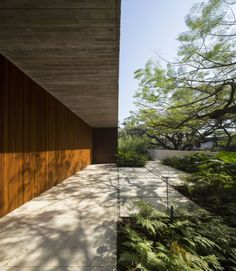 Haus Garten Baukörper Pflastersteine lauschige Pflanzen Betonmauer Bäume