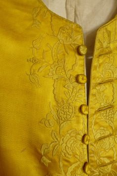 Detail: Waistcoat, (Chinese Export Market), 1760s, bright Imperial yellow satin with round neck, the curved front opening border embroidered in twisted silks with peonies and fruits in a leaf meander, continuing to the skirts.