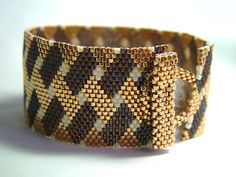 """Decadence"" cuff by Anna (ARoseByName). Peyote stitch with self toggle clasp. Delica beads (matte choc brown AB, opaque cream AB, metallic gold). ""After I started it, I thought it look rich and decadent...then I thought it looked like S'mores!"""