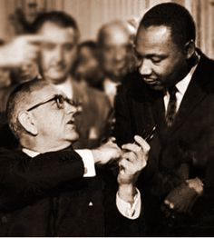President Lyndon Johnson, after signing the Civil Rights Act, gives the first pen to Martin Luther King, Jr.