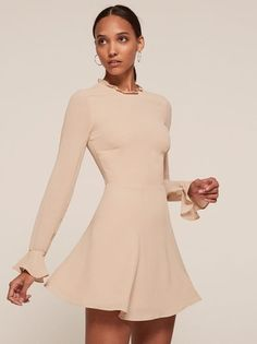 This is a high neck, fit and flare dress with a removable belt, a ruffled neckline and bell sleeves.