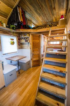 The stairs, the angled door, and the loft all make this woodsy tiny house cozy. | Tiny Homes