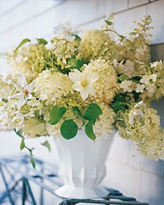 Celebrate big, billowing flowers with an exuberant large-scale arrangement. This display showcases the unrestrained beauty of hydrangeas. An armful of the flowers overflows a generous glazed-iron urn-shaped vase in an effortlessly elegant way. Tendrils of clematis winding through the blooms emphasize the cottage-garden feeling.