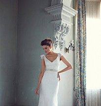 Demi Couture V-neck corded lace slim line gown with lace cap sleeves and sheer lace back finished with a waist tie.