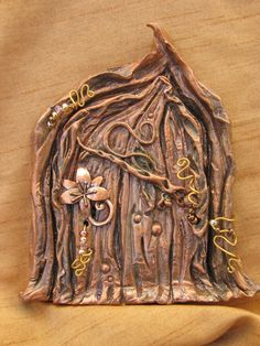 """Overview • Materials: air dry clay, acrylic paints, beads, trinkets, key, charms, magic • Ships worldwide from United States • Favourited by: 11 people  Item Details This Faerie Secrets Door is part of my brand new ENCHANTED FOREST collection!     This door is a SECRET Faerie Door...It has a removable key with a charm that is imprinted with """"Ancient Faerie Writing"""". Flip the charm over to see what secret word must be said to use this mystical portal! Only YOU will know what the secret word…"""