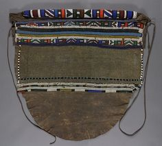 Back Apron (thimba) Physical Description: Leather, glass beads, metal studs, fiber 27 x 28 in. (68.6 x 71.1cm) Creator: Ndebele People, 20th Century gallery notes: The thimba, or back apron, complements a type of skirt worn on the front, either an itshogolo or a mapoto, which identifies the wearer as a married woman. The top of the thimba is rolled over a straw core, and heavily beaded with imported glass seed beads and brass beads. The use of brass for prestigious items of personal ...
