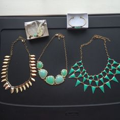 5-Piece Turquoise Jewelry Set A 5-piece set of turquoise jewelry, consisting of two bracelets and three necklaces. The bracelets are classy gold pieces with a subtle hint of turquoise, while the necklaces are dramatic statement pieces. Jewelry