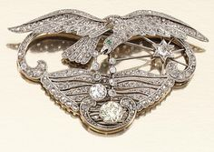 EMERALD AND DIAMOND BROOCH/PENDANT, EARLY 20TH CENTURY Of pierced open work design, millegrain-set throughout with rose-, single- and circular-cut diamonds, depicting a bird of prey in flight holding an articulated pair of collet-set circular- cut diamond drops of near-colourless and yellow tints respectively, its eye embellished with a cabochon emerald, one diamond point deficient, brooch fittings detachable.