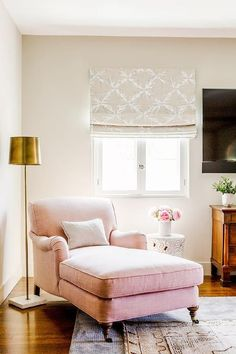 Master bedroom features reading corner filled with a pink linen roll arm chaise lounge next to a white cloud stool illuminated by brass and marble floor lamp placed under window.