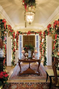 foyer is decked in ribbons, bows and garland and glistens with white lights.