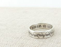 The mountains are calling... A simple silver ring with a serene mountain pattern on the exterior and The Mountains Are Calling And I Must Go engraved inside. You can change the interior inscription to                                                                                                                                                                                 More