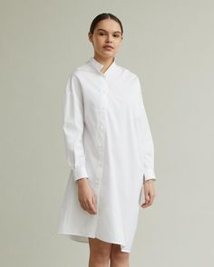 A long sleeve poplin shirt dress featuring a playful deconstructed silhouette and offset button closure. Stand collar Straight hem Relaxed fit cotton Model is 175 ft 7 in and is wearing a size XS in white Deconstruction, Apothecary, Designing Women, Poplin, Silhouette, Closure, Shirt Dress, Button, Long Sleeve