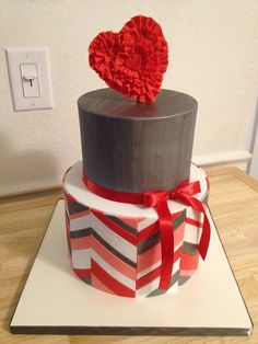 """Be My Valentine <3 Offset Chevron - Offset Chevron in Valentine colors (8""""), grey fondant painted w/ dark silver luster and silver highlighter (6""""), 50/50 ruffled heart topper.  Cake design inspired by class Jessica Harris did on Craftsy :)"""