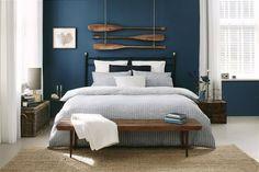 Déco graphique et naturelle, avec des rames suspendues en guise de décor de tête de lit. Évocation de la mer en lien avec le bleu profond des murs et le jonc de mer au sol.