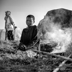 """Early morning hope. From my series: """"Beauty In Hell - Beauty over Drama"""". #beautyinhell. A young girl at the sunrise in the refugee camp outside Mogunda. She is preparing food for the rest of her family 2 brothers and a sister. In these camps the conditions are very hard and most of the people have some form of illness to cope with. ---------------------------------- WEBSITE: www.tonycorocher.com FB: http://ift.tt/1UzRMvm PRINT SHOP: http://ift.tt/1RIs7xT…"""
