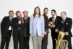 Mnozil Brass.  These guys have both boundless skill and humor.  Pick anything at random on Youtube by these fellows and you're sure to be entertained.  No musical genre is too serious to avoid a good lampooning and no instrument too sacred to keep from being used in a silly fashion.
