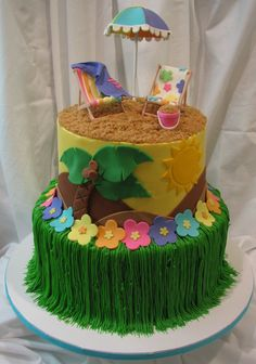 """Luau - This cake was done for a little girls backyard Luau themed birthday party. The cake is done in buttercream with fondant accents. The """"grass skirt"""" was piped with buttercream with fondant flower accents. The beach umbrella, chairs and sand pail were done in gumpaste. The """"sand"""" is brown sugar."""