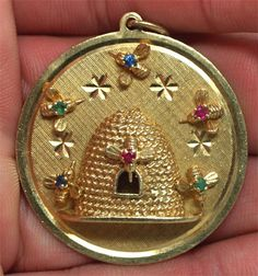 Gemstone studded honey bees buzz around a high relief hive in this great pendent/charm. The bee's bodies are made of natural rubies, emeralds and sapphires Bee Jewelry, Insect Jewelry, Jewellery, Antique Jewelry, Hives And Honey, Honey Bees, Vintage Charm Bracelet, Charm Bracelets, I Love Bees
