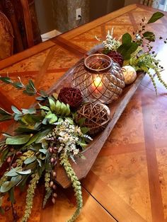 a bread bowl with wicker balls, acorns, greenery and white blooms as a centerpiece