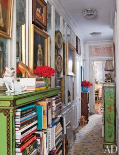 A hallway is lined with dog paintings and 19th-century English bookcases brimming with volumes on fashion, decorative arts, and Chinese costumes and textiles.